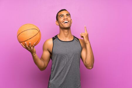 Young sport man with ball of basketball over isolated purple wall pointing up a great idea