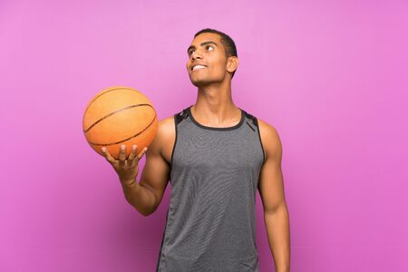 Young sport man with ball of basketball over isolated purple wall looking up while smiling