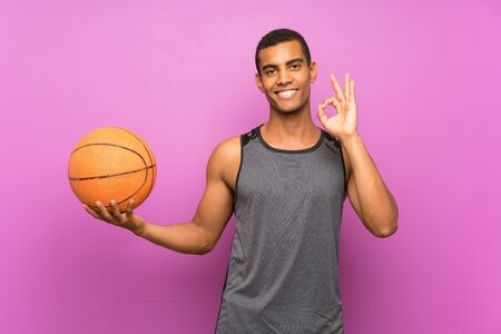Young sport man with ball of basketball over isolated purple wall showing ok sign with fingers Banque d'images