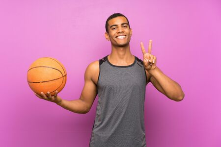 Young sport man with ball of basketball over isolated purple wall smiling and showing victory sign