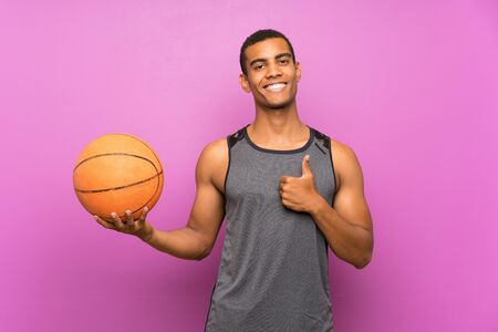 Young sport man with ball of basketball over isolated purple wall with thumbs up because something good has happened