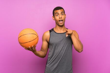Young sport man with ball of basketball over isolated purple wall surprised and pointing front