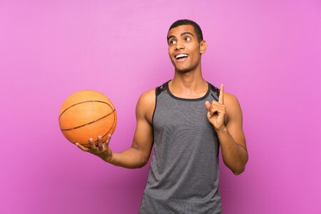 Young sport man with ball of basketball over isolated purple wall intending to realizes the solution while lifting a finger up