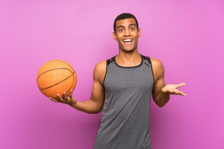 Young sport man with ball of basketball over isolated purple wall with shocked facial expression Banque d'images