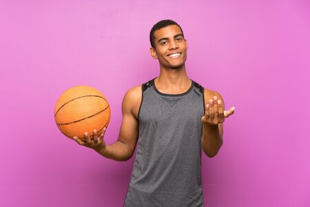 Young sport man with ball of basketball over isolated purple wall inviting to come with hand. Happy that you came