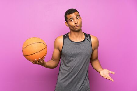 Young sport man with ball of basketball over isolated purple wall making doubts gesture while lifting the shoulders