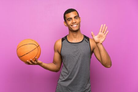 Young sport man with ball of basketball over isolated purple wall saluting with hand with happy expression Standard-Bild