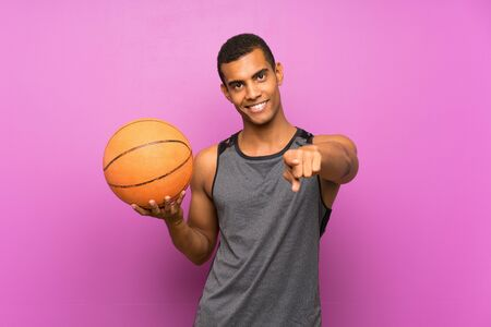 Young sport man with ball of basketball over isolated purple wall points finger at you with a confident expression