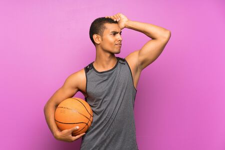 Young sport man with ball of basketball over isolated purple wall having doubts and with confuse face expression