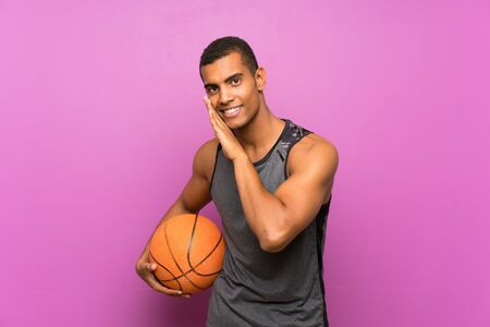 Young sport man with ball of basketball over isolated purple wall whispering something Standard-Bild