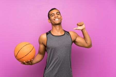 Young sport man with ball of basketball over isolated purple wall proud and self-satisfied