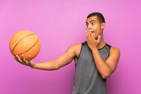 Young sport man with ball of basketball over isolated purple wall with surprise and shocked facial expression