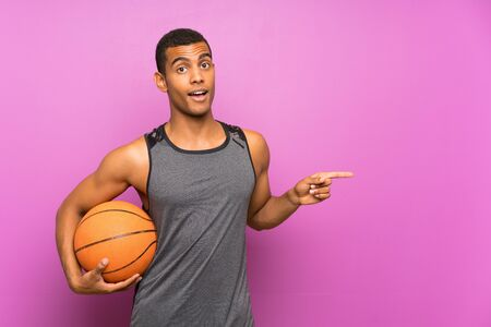 Young sport man with ball of basketball over isolated purple wall surprised and pointing finger to the side Standard-Bild
