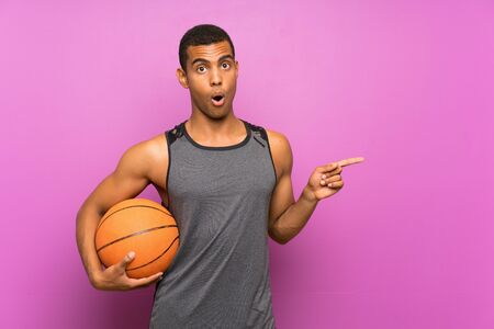 Young sport man with ball of basketball over isolated purple wall surprised and pointing side