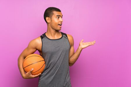 Young sport man with ball of basketball over isolated purple wall with surprise facial expression