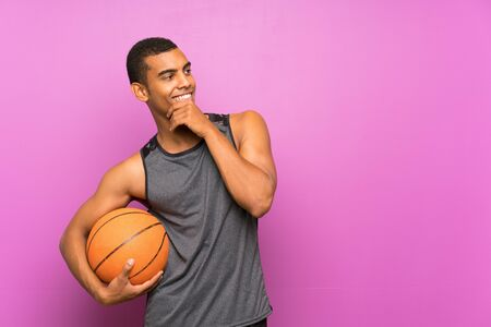 Young sport man with ball of basketball over isolated purple wall thinking an idea and looking side Banque d'images