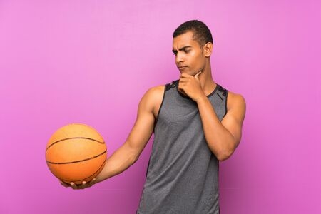 Young sport man with ball of basketball over isolated purple wall with sad expression Standard-Bild