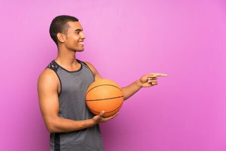 Young sport man with ball of basketball over isolated purple wall pointing to the side to present a product