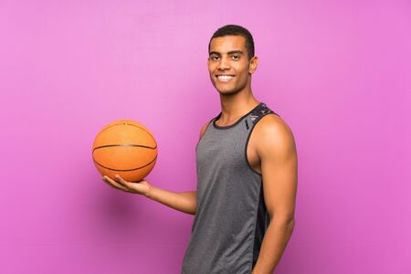 Young sport man with ball of basketball over isolated purple wall smiling a lot Banque d'images