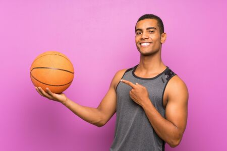 Young sport man with ball of basketball over isolated purple wall and pointing it