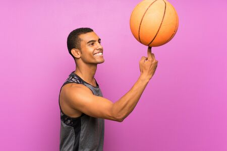 Young sport man with ball of basketball over isolated purple wall