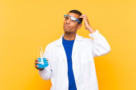 Scientific man holding a laboratory flask over isolated background having doubts and with confuse face expression Standard-Bild