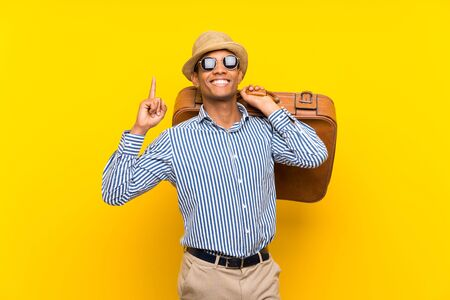 Brunette man holding a vintage briefcase over isolated yellow background pointing up a great idea