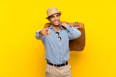 Brunette man holding a vintage briefcase over isolated yellow background surprised and pointing front