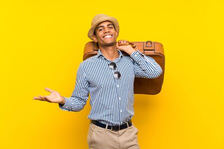 Brunette man holding a vintage briefcase over isolated yellow background with shocked facial expression