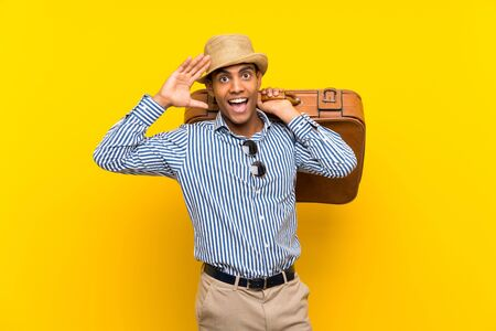 Brunette man holding a vintage briefcase over isolated yellow background with surprise and shocked facial expression