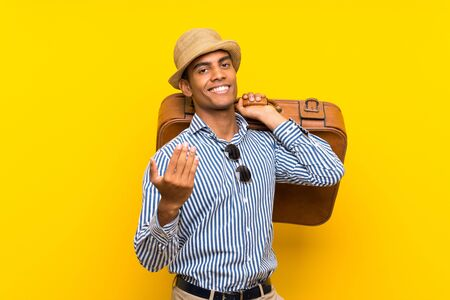 Brunette man holding a vintage briefcase over isolated yellow background inviting to come with hand. Happy that you came