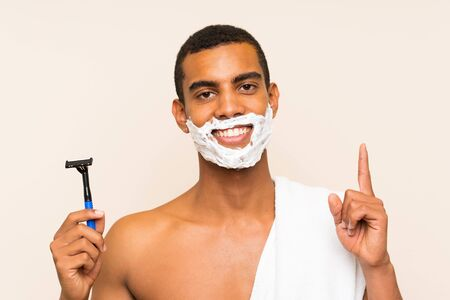 Young handsome man shaving his beard over isolated background pointing up a great idea