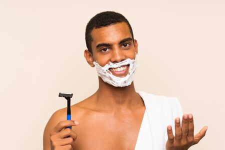 Young handsome man shaving his beard over isolated background inviting to come with hand. Happy that you came