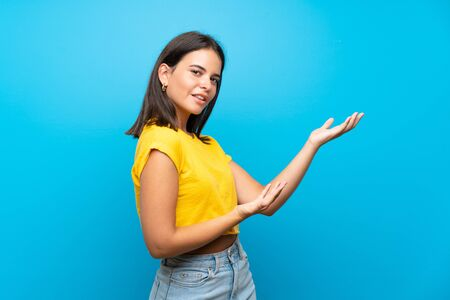 Young girl over isolated blue background extending hands to the side for inviting to come Standard-Bild