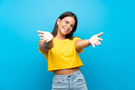 Young girl over isolated blue background presenting and inviting to come with hand