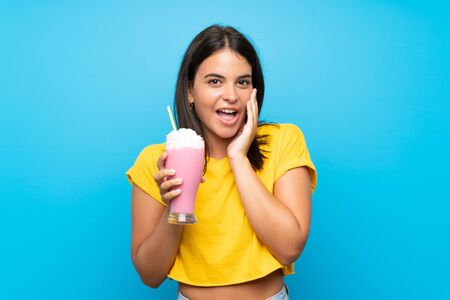 Young girl with strawberry milkshake over isolated background with surprise and shocked facial expression