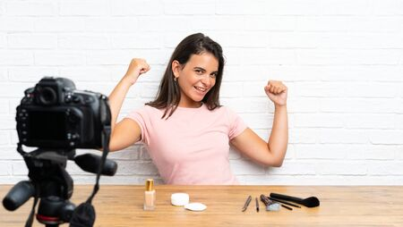 Young girl recording a video tutorial celebrating a victory
