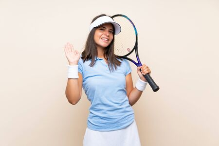 Young woman playing tennis over isolated background saluting with hand with happy expression