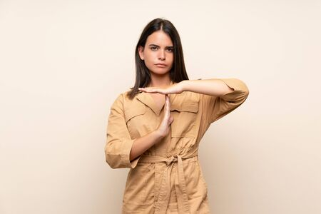 Young girl over isolated background making time out gesture