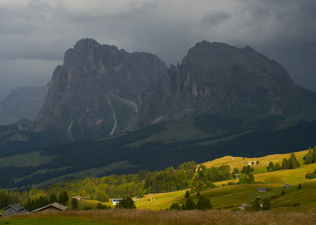 Sassolungo mountains on the Italian Alps Dolomites on the shadow with the sunlight appearing on the landscape