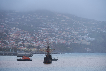 View of Funchal, Madeira from the Marina with a caravel boat on the sea Archivio Fotografico