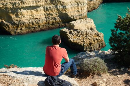 Man looking at a wild hidden secret beach with amazing turquoise water in Algarve, Portugal