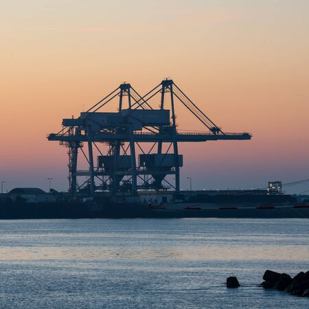Sines container port terminal with cranes at sunset, in Portugal Stock Photo