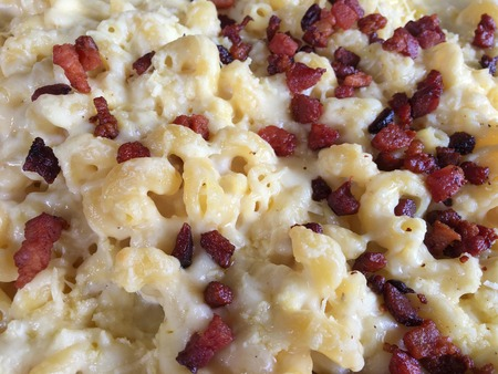 Pasta topped with melted cheese and bits of fried bacon