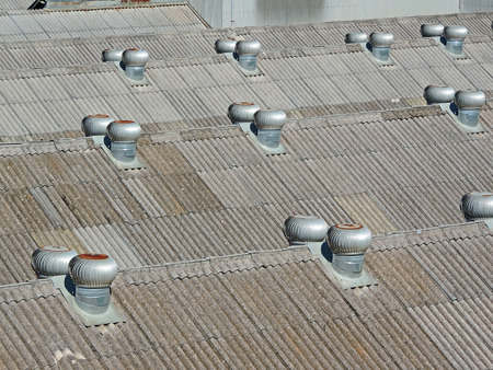Roofs of industrial sheds covered with gray tiles and exhaust system Stock Photo
