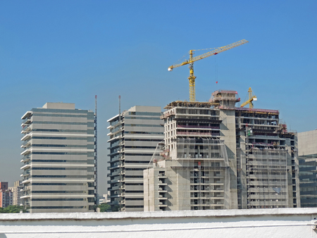 A building under construction with coupled cranes