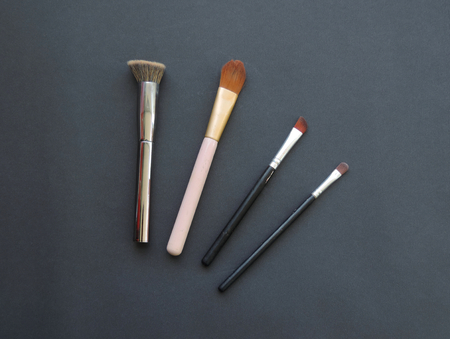 A set of makeup brushes on dark background