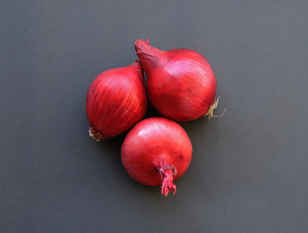 Three red onions on the dark background