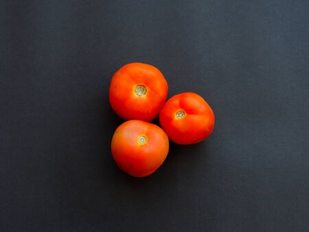 Three red tomatoes isolated on dark background
