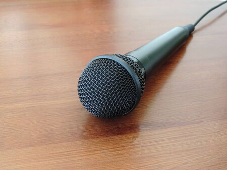 A Microphone left on the wooden table Imagens